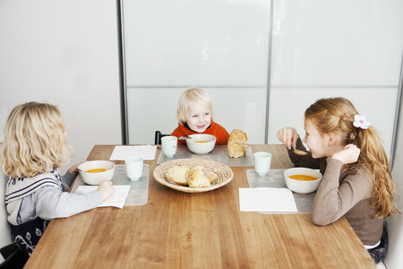 negative area: Children eating lunch at table LANG_EVOIMAGES