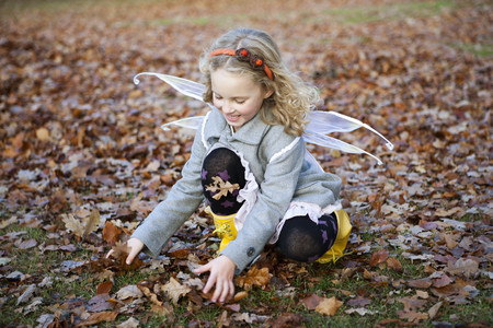 agachado: Chica en alas de hadas jugando en hojas