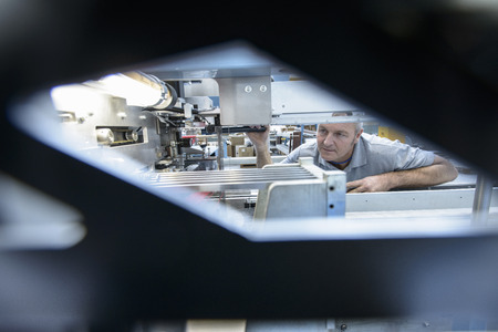 power operated: Worker using machinery in textile mill LANG_EVOIMAGES