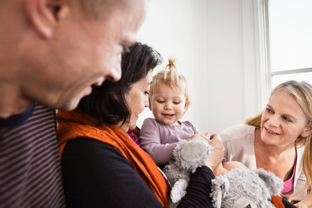 three months old: Grandmother holding toddler granddaughter with parents LANG_EVOIMAGES