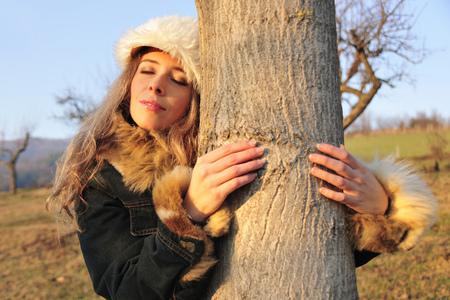 environmentalism: Woman in fur hat hugging tree LANG_EVOIMAGES