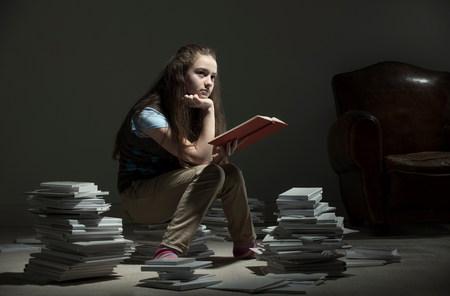 Mädchen sitzt auf Haufen Bücher lesen