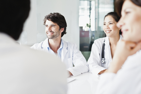 Doctors smiling in meeting LANG_EVOIMAGES