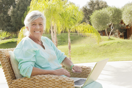 communicated: Older woman using laptop outdoors LANG_EVOIMAGES