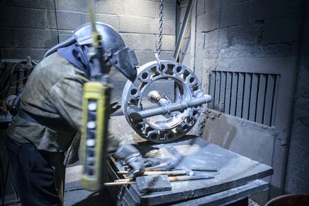 preparedness: Worker preparing to cut metal in foundry