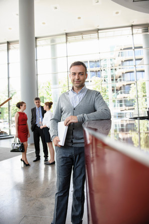 receptions: Businessman holding laptop leaning against reception desk LANG_EVOIMAGES