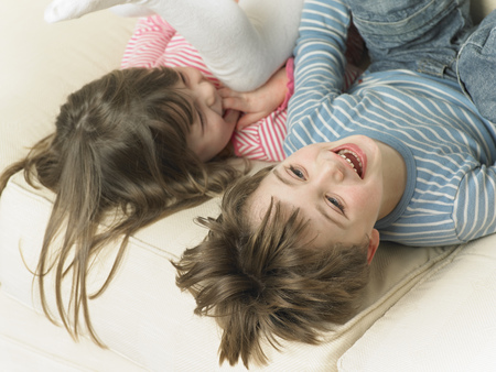 Children playing on sofa together LANG_EVOIMAGES