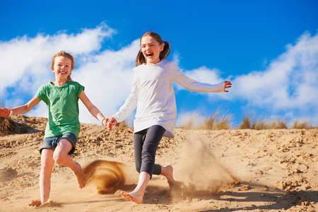 Two girls running down sand dune