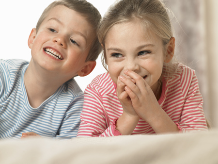 enthusiastically: Children laughing together on bed