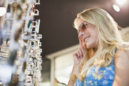 Woman trying on sunglasses in store