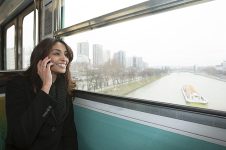 responding: Smiling woman riding train over water LANG_EVOIMAGES