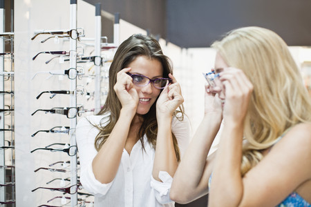resolving: Women trying on glasses in store