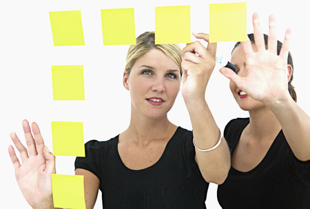 notations: Businesswomen making sticky notes