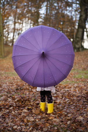 defended: Girl playing with umbrella in park LANG_EVOIMAGES