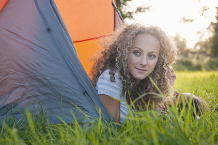 Teenage girl laying in tent at campsite LANG_EVOIMAGES