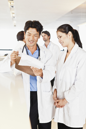 Doctor reading his notes to colleague