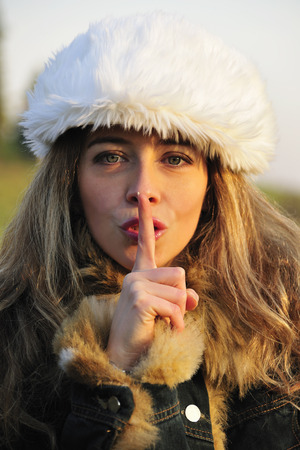 hushed: Woman holding finger to lips outdoors LANG_EVOIMAGES