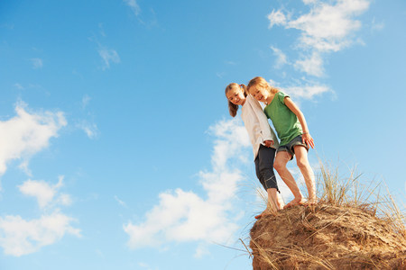 Two girls standing on edge of sand dune,low angle