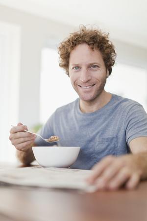 Man reading newspaper at breakfast LANG_EVOIMAGES