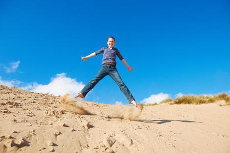 Teenage girl jumping on sand LANG_EVOIMAGES