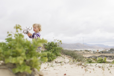 bough: Girl playing with twigs on beach LANG_EVOIMAGES