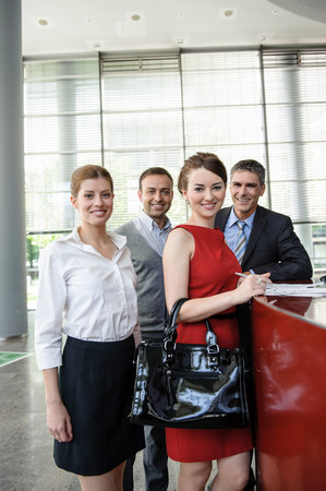 receptions: Group of business people with documents on reception desk LANG_EVOIMAGES