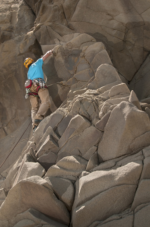 Rock climber scaling jagged cliff