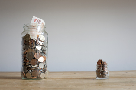 Large and small savings jars on desk