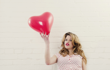 Woman holding heart shaped balloon LANG_EVOIMAGES