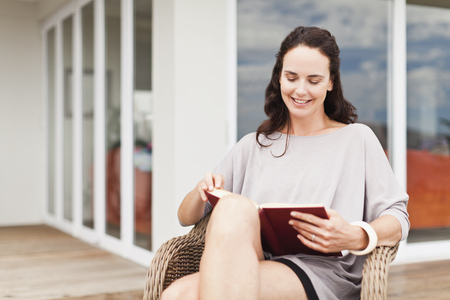 tomes: Woman reading book in backyard