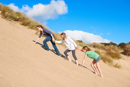 Three girls climbing up sand dune