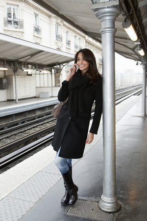 通信: Woman on cell phone at train station LANG_EVOIMAGES