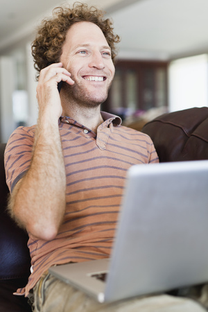 reconocimientos: Hombre en la computadora portátil hablando por teléfono celular LANG_EVOIMAGES