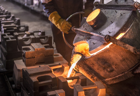 maneuvering: Worker pouring molten metal in foundry