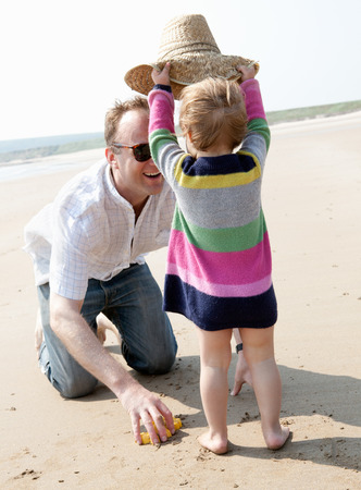 whimsy: Girl putting hat on father at beach