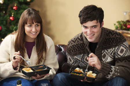 customs and celebrations: Couple eating microwave dinners on sofa