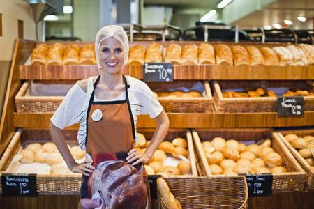 womens hands: Baker smiling in store LANG_EVOIMAGES