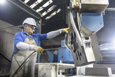 somber: Worker cleaning mould in metal foundry