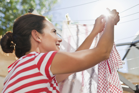 Woman hanging clothes up on line LANG_EVOIMAGES