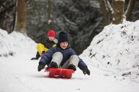 to go sledding: Children sledding on snowy slope