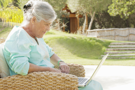grey eyed: Older woman using laptop outdoors LANG_EVOIMAGES