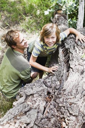 preadolescent: Father helping son over fallen tree