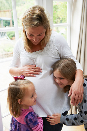 kick around: Pregnant mother with two daughters LANG_EVOIMAGES