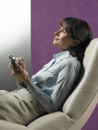 通信: Businesswoman using cell phone