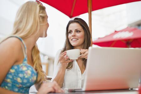 通信: Women using laptop at sidewalk cafe
