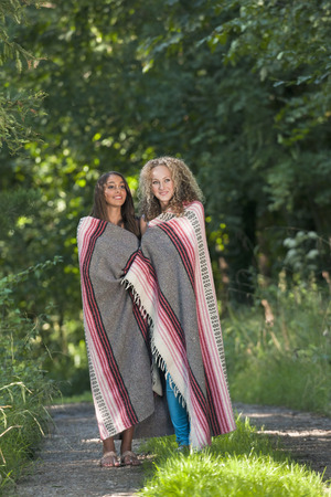 shared sharing: Teenage girls in blanket on rural road