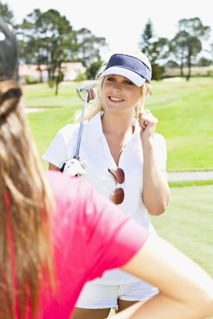 Women playing golf together on course