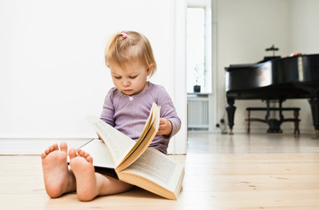 Toddler girl sitting on floor reading book