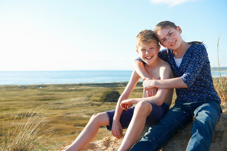 Boy and teenage girl sitting on beach LANG_EVOIMAGES