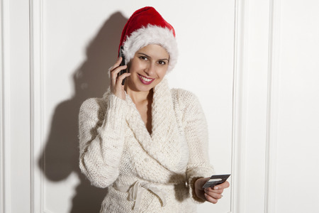 require: Woman in Santa hat talking on cell phone